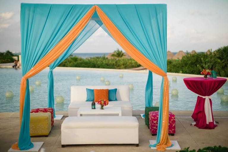 White couch under a blue and orange canopy in front of the water. Pink covered cocktail tables are off to the sides