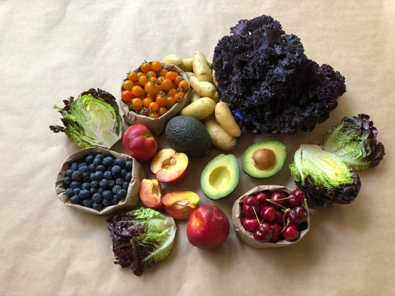 Fresh fruit and veggies on a taupe tablecloth.