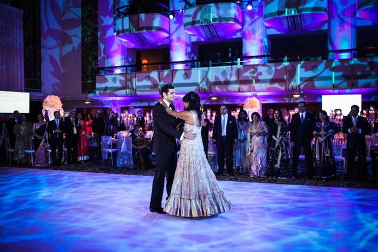 A blue and purple lit dancefloor with the couple