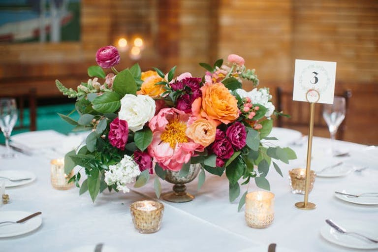 An arrangement of pink and orange flowers with greenery and candles around them on a white linen