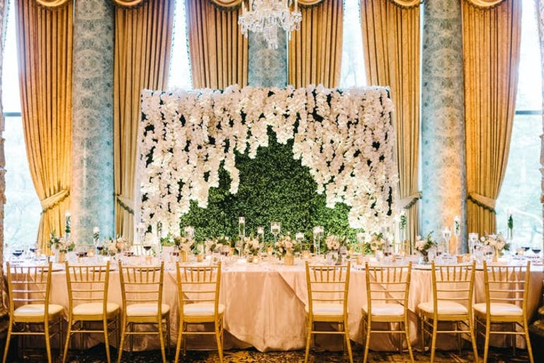 windows with gold drapes behind a rectangular table. A greenery backdrop is behind the table and is flanked with white flowers
