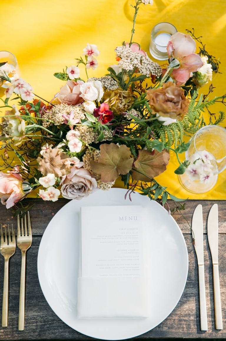 White plate with a bright yellow table runner and muted toned florals