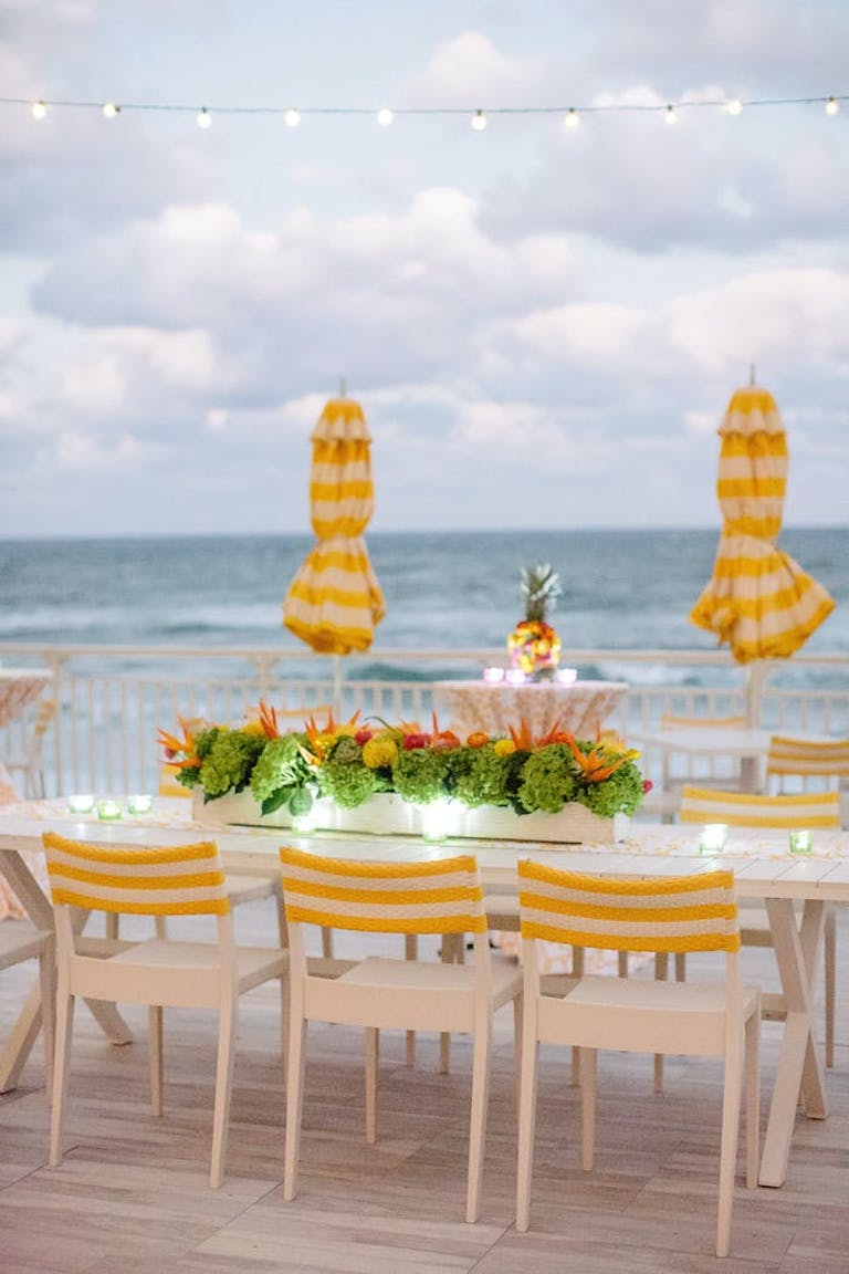 A waterfront table with yellow and white striped chairs and a matching umbrella. Greenery as the centerpiece with colorful florals