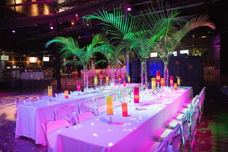 two long tables with white linens and palm leaves acting as center pieces