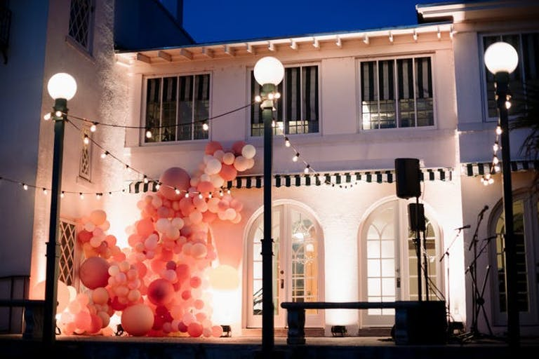 A white building with three lamp posts in front. Pink and coral balloon installations look as if they are growing on the building like ivy