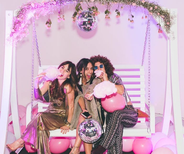 Three girls sit in a swinging bench with a pink backdrop holding disco balls and eating cotton candy | PARTYSLATE