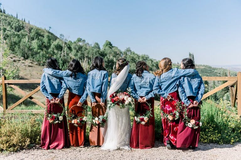Bridal party looking out onto a grand landscape in red dresses with denim jackets