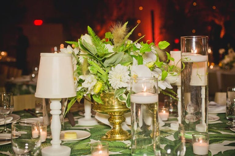 white lamps as centerpieces with greenery in the middle.