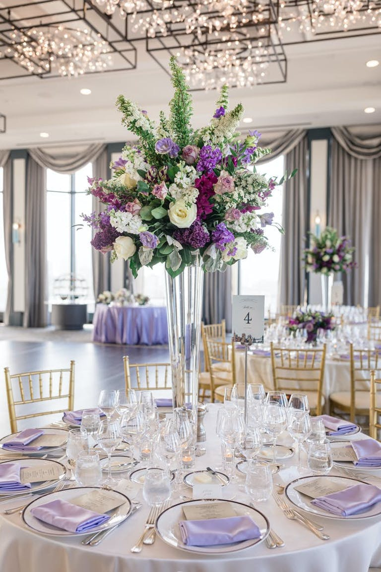A white linened table with purple accents and tall centerpieces