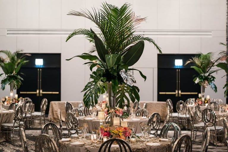 A ballroom with white walls and round tables and tall greenery as the centerpieces