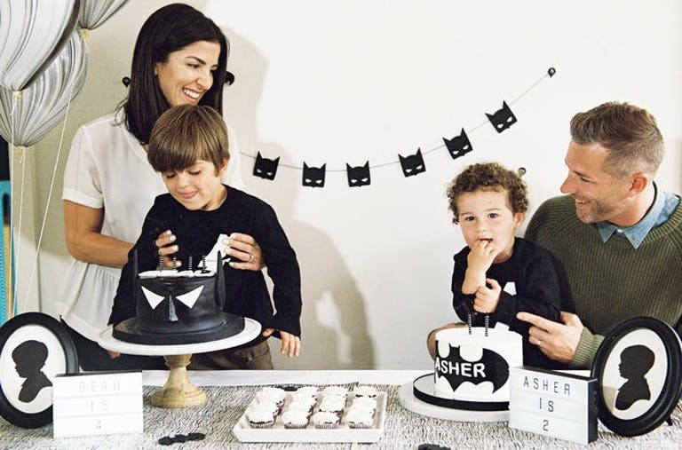 A mom, dad, and two little boys celebrate a joint Batman-themed birthday for their sons.