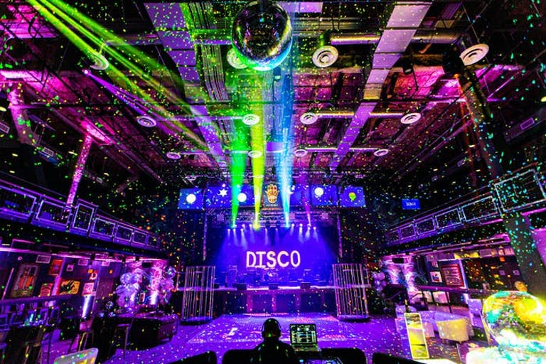 A room full of confetti and lighting shines towards a disco sign | PartySlate