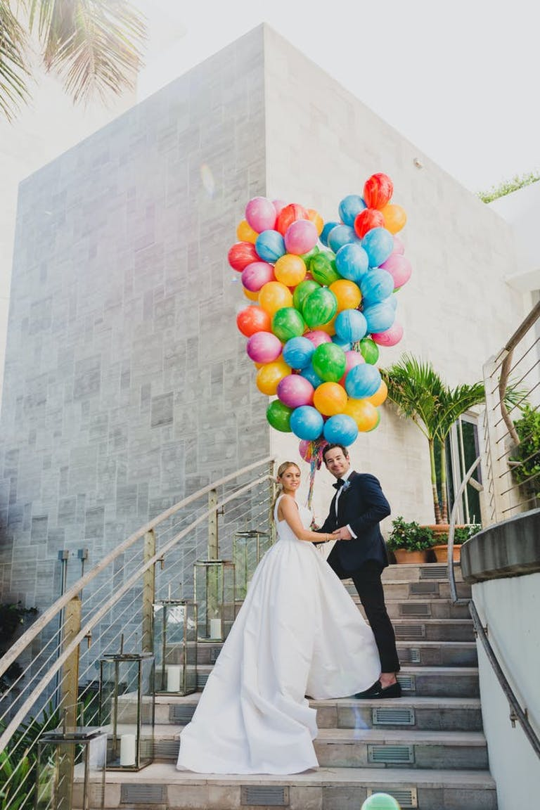 A couple posing on a winding staircase with a balloon bouquet mad of pink, blue, green, and yellow balloons