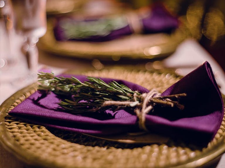 a wicker charger with purple napkin on top with sage layed on it