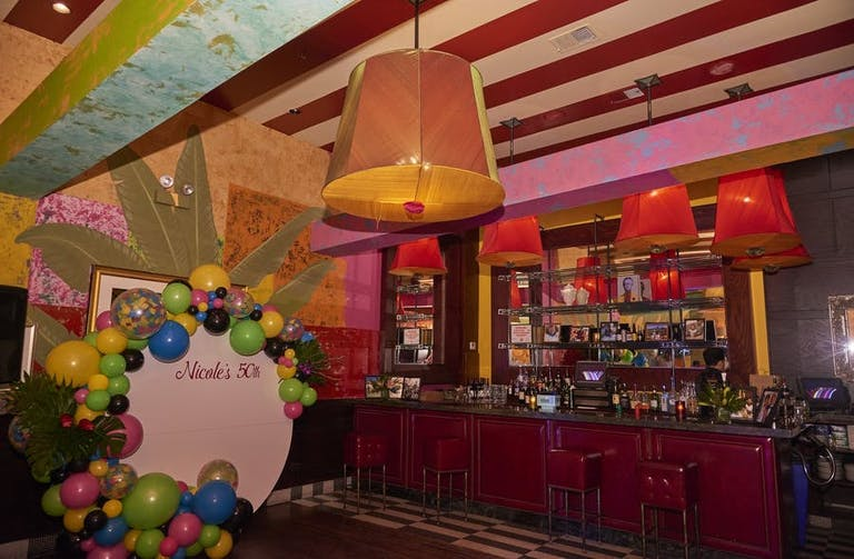 A dim bar on the right with bottles along the inside. A photo backdrop to the left with a multicolor balloon border.