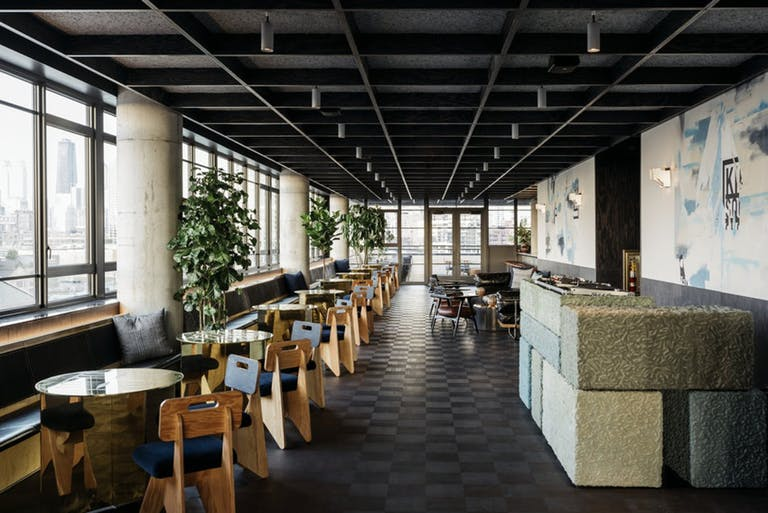 Indoor rooftop bar with floor to ceiling windows on left side of photo.
