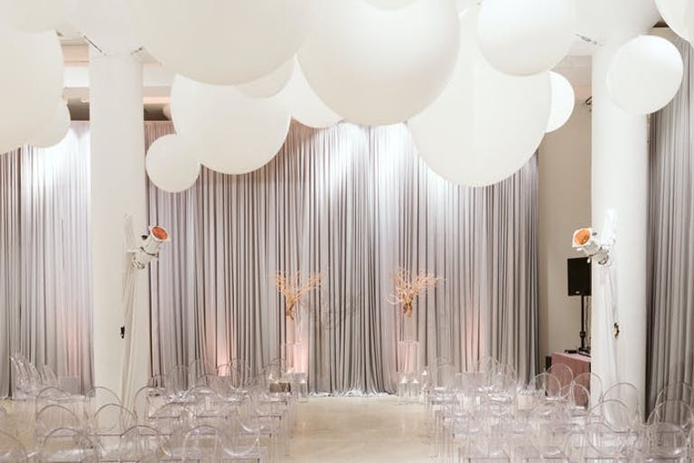 A white room with wide white columns and a white curtain. White decor sits in front of the curtain and large circular balloons float to the ceiling