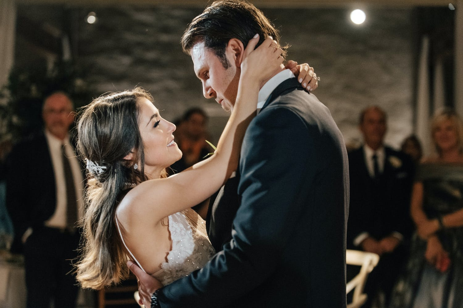 Close up of bride cupping groom's face while dancing.
