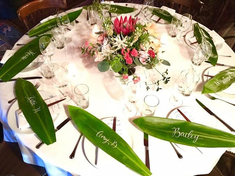 A round table with a white linen and colorful low centerpiece. Long green leaves with white calligraphy act as place cards