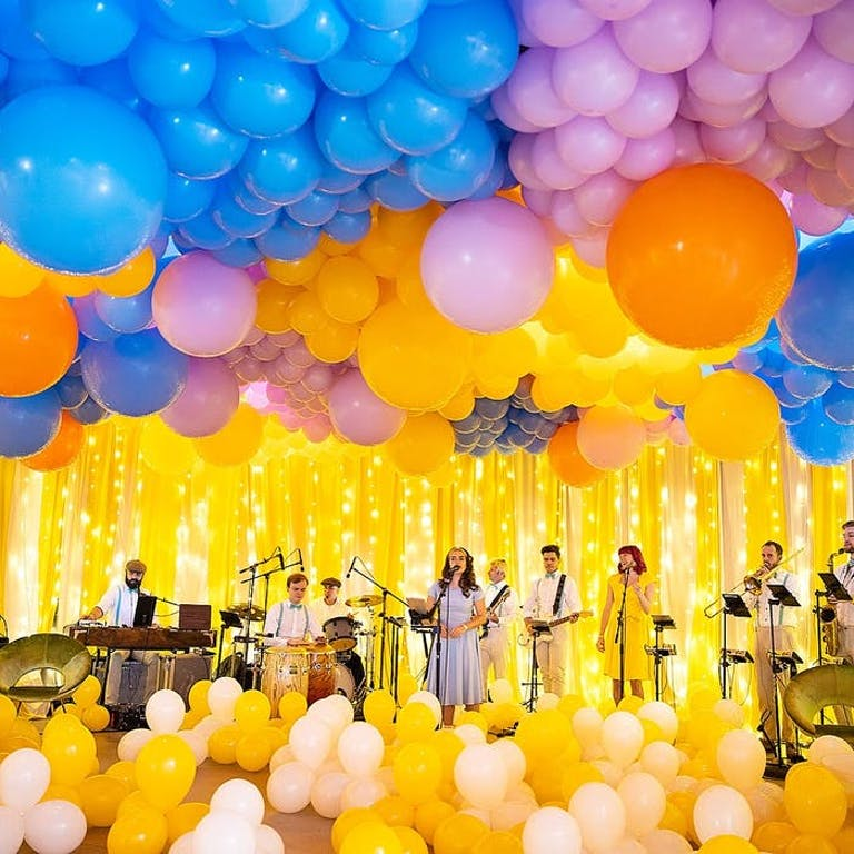 A stage covered in yellow balloons and yellow tinsel with blue and pink balloons covering the ceiling