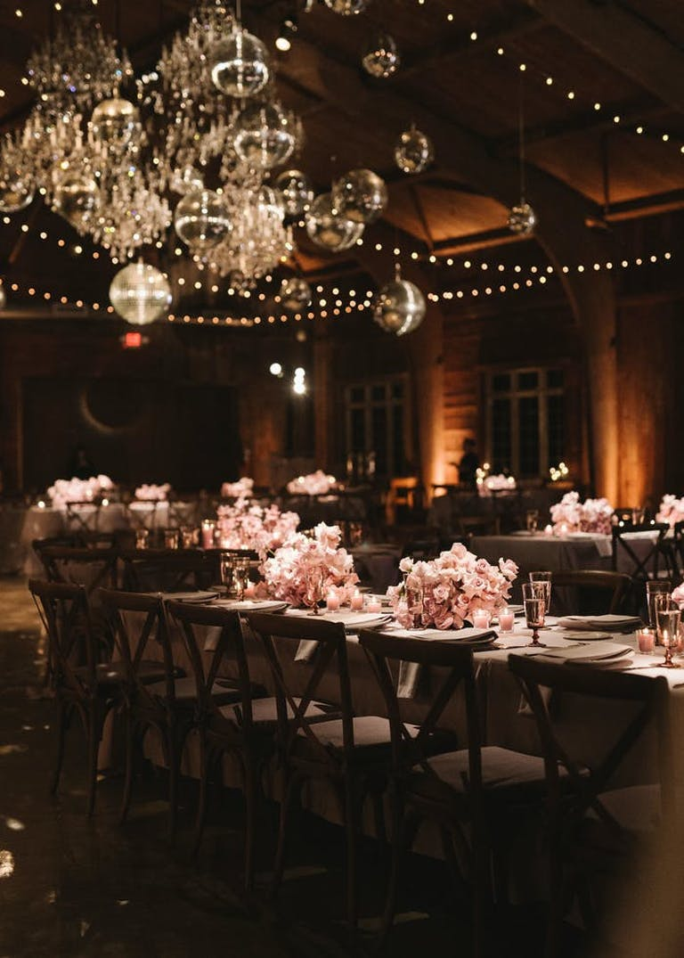 Tables of varying heights with pink florals. In the corner there is a cluster of different sizes disco balls with golden light shining on them | PartySlate