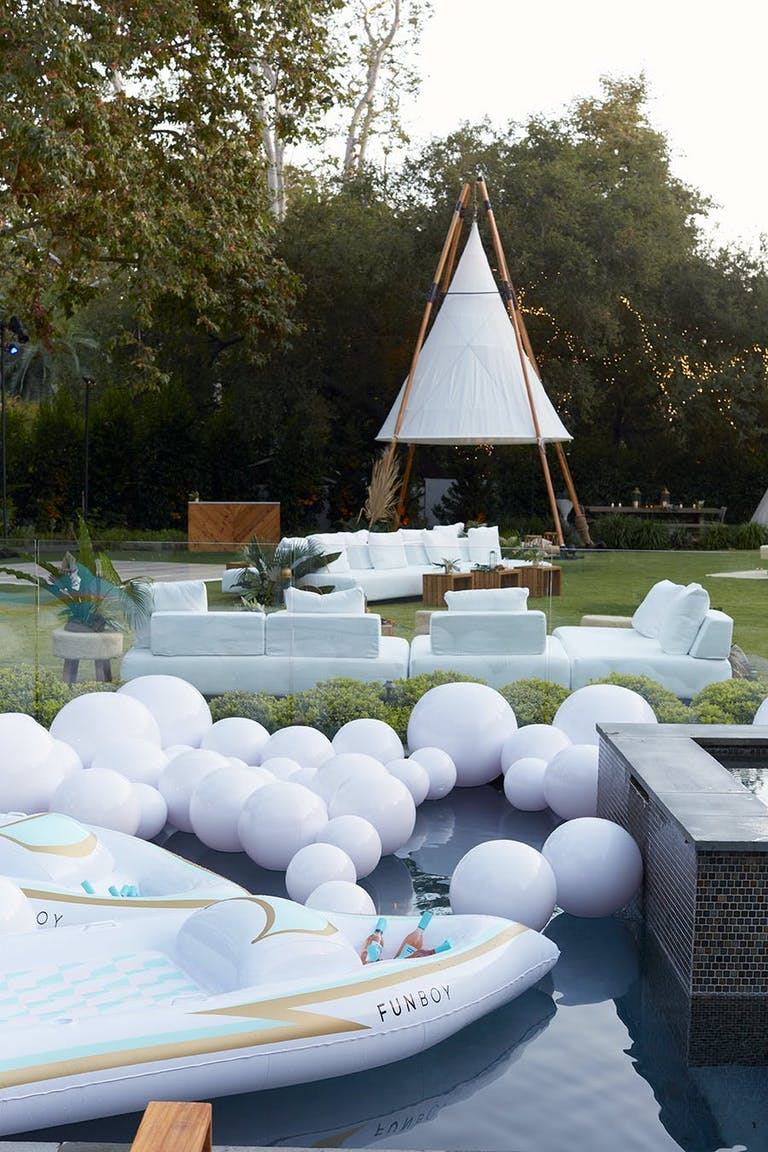 a pool with white balloons floating on top. In the background is a white tent with couches