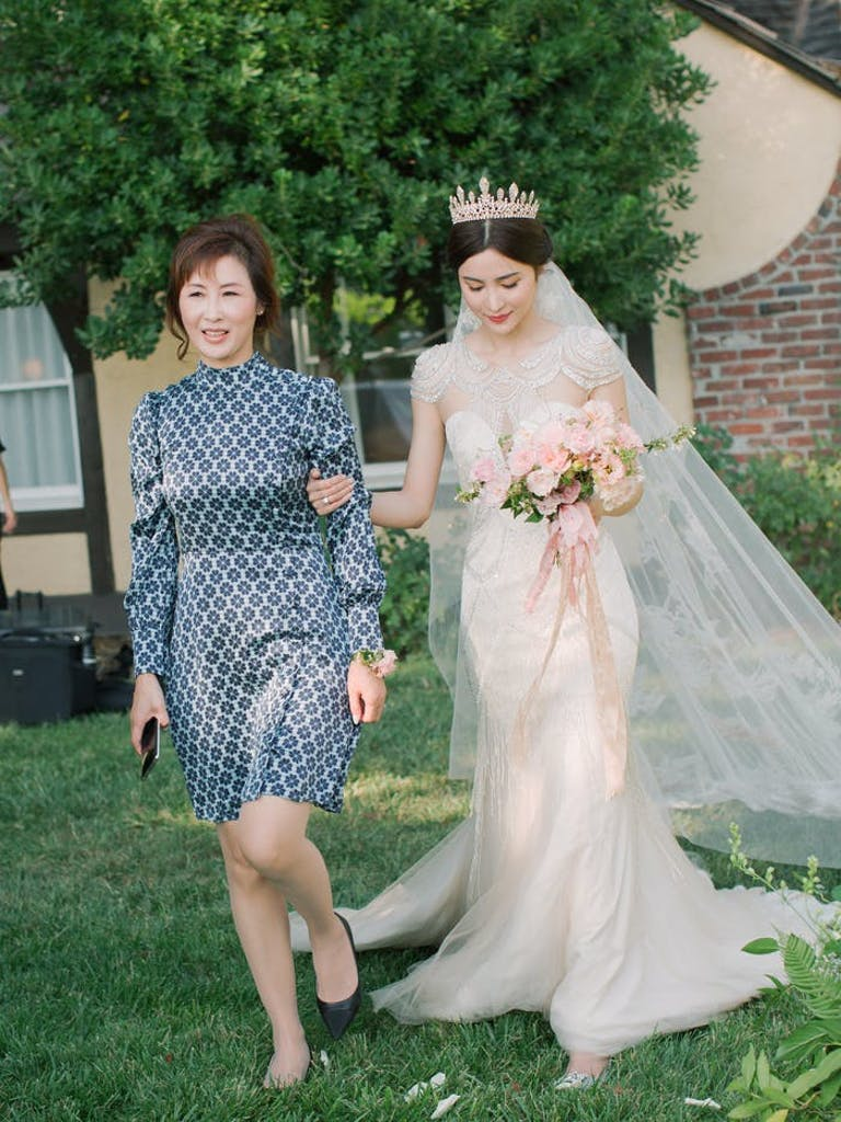 A mom leads her daughter to the aisle wearing a silver dress. There is grass and a tree behind them