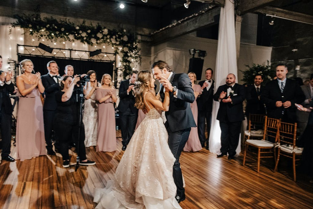 Bride and groom dance, surrounded by loved ones,  in raw industrial space with a backdrop of white roses and greenery.