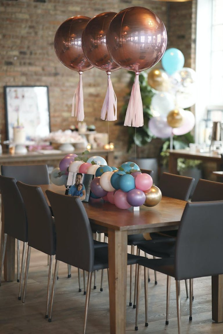 a table with colorful balloons with tassels