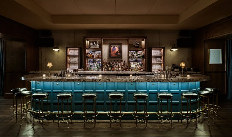 Dimly lit speakeasy bar with wrap around bar with blue side-paneling and leather stools.