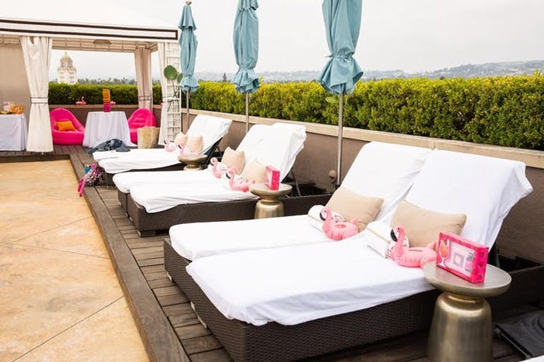 A rooftop patio looking over the landscape. White lounge chairs and pink pillows line the wall