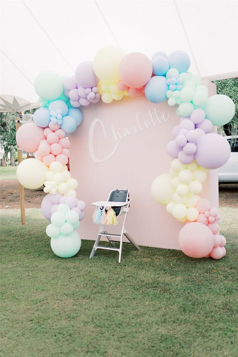 A dusty pink backdrop surrounded by different color pastel balloons.