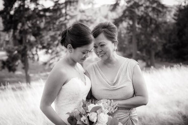 A black and white photo of a mother and daughter outside in a meadow embracing each other