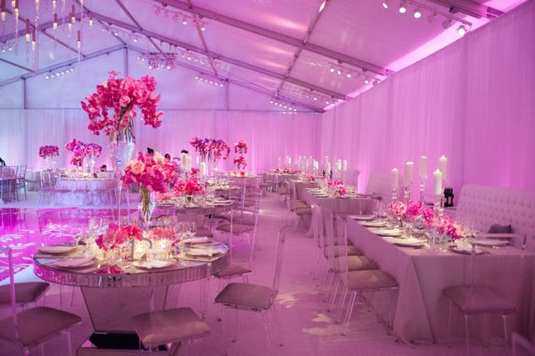Room lit up pink with tall pink floral centerpieces