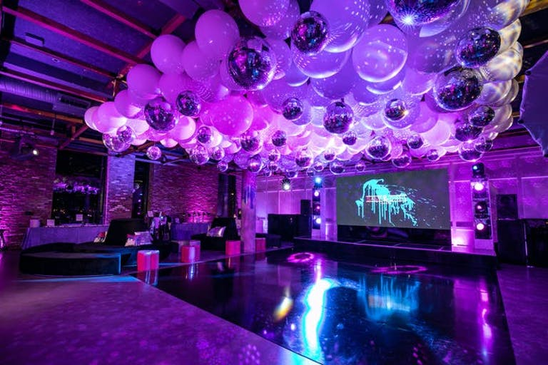 A purple washed room with balloons on the ceiling over the dance floor and a screen displaying blue lighting for disco-themed party | PartySlate