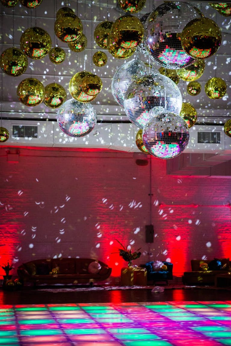 Disco-Themed Party With Disco Ball Ceiling Installation and Colorful LED Dance Floor | PartySlate