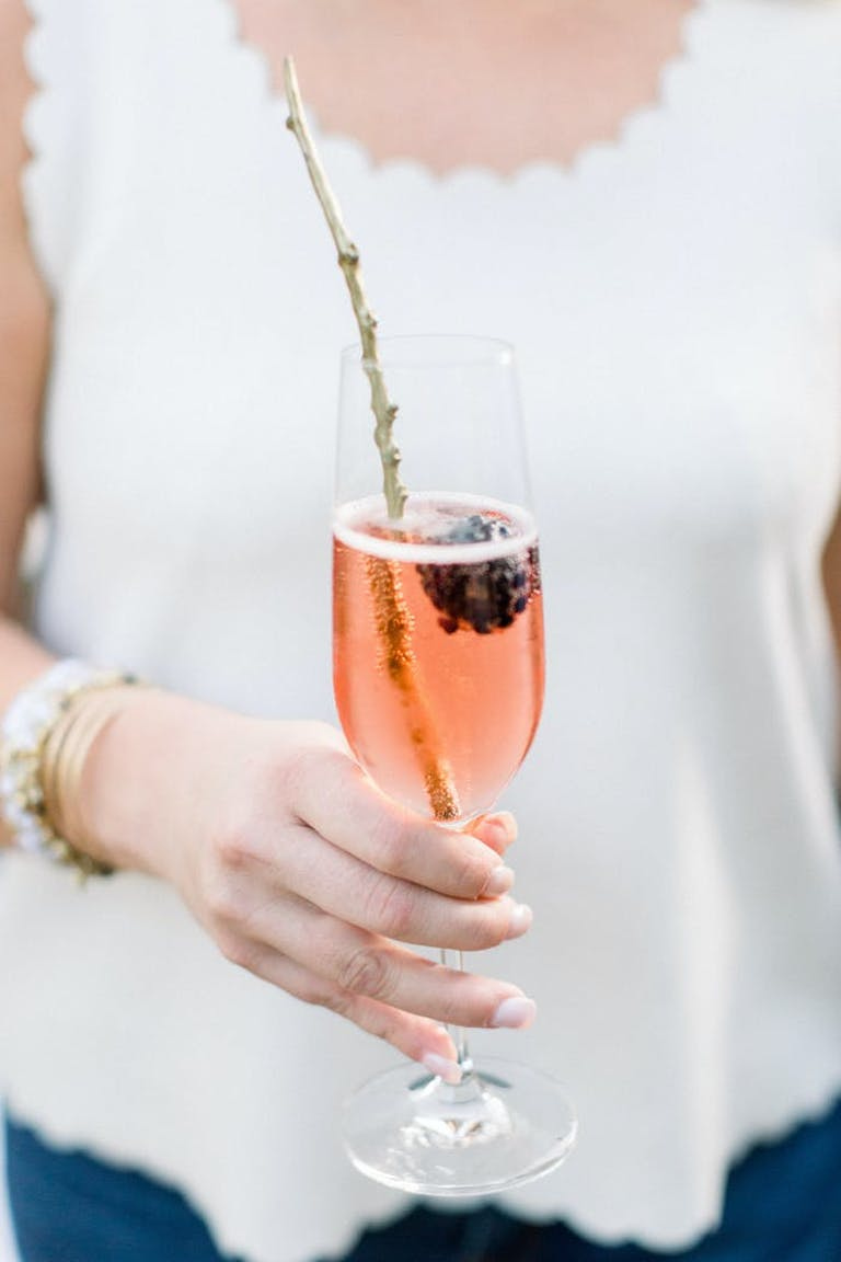 woman in a white tank holding a pink drink in a champagne flute. A branch is used as garnish
