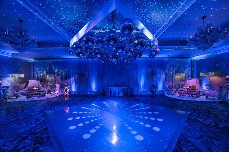 A blue washed room with white beams of light shining on the dance floor | PartySlate