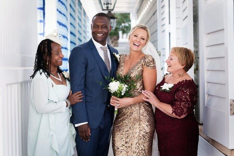 A bride and groom take a picture with their mom on each side in a quiet outdoor corridor.
