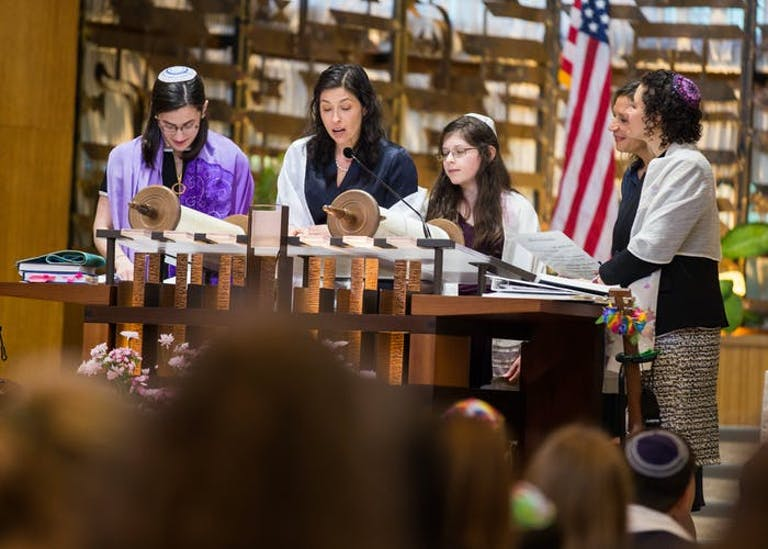 A mom reads Torah at the Bimah with her son and daughter.