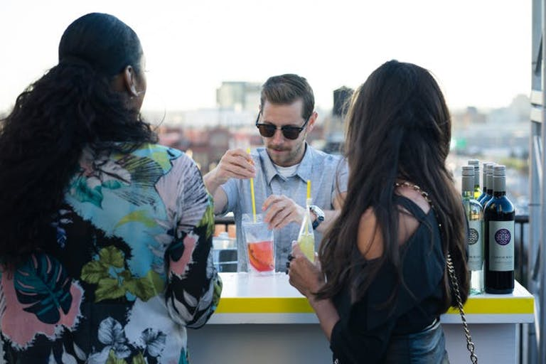 A bartender in the center placing straws in a drink while two women stand on either side of him