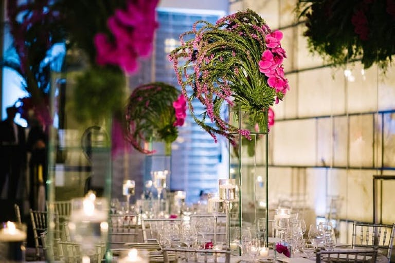pink and green tall floral arrangements sit on each table