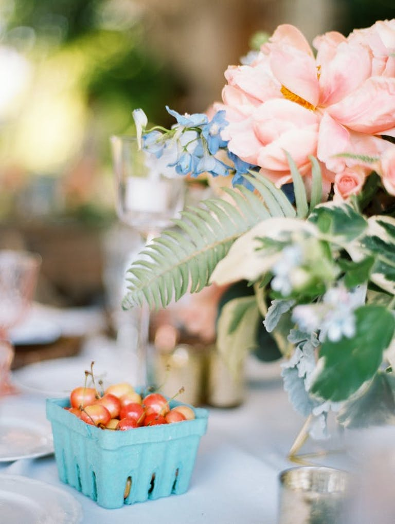 pink and green centerpieces with tomatoes in a blue carton underneath