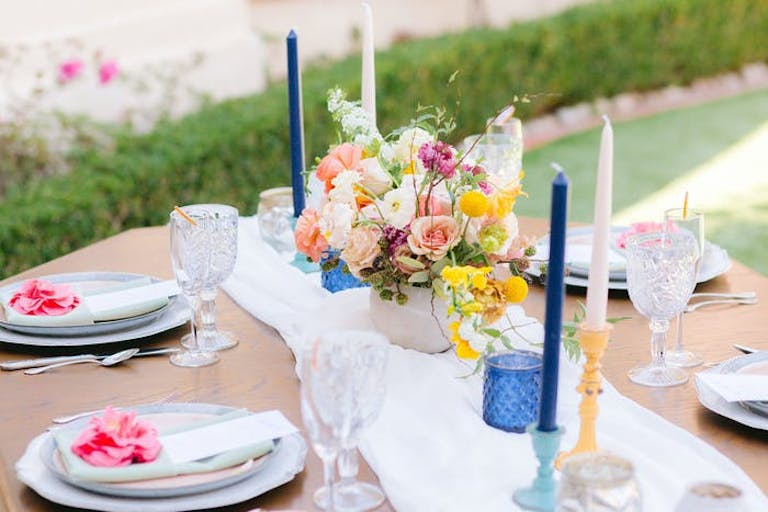 white tables scape with colorful candle holders with pillar candles
