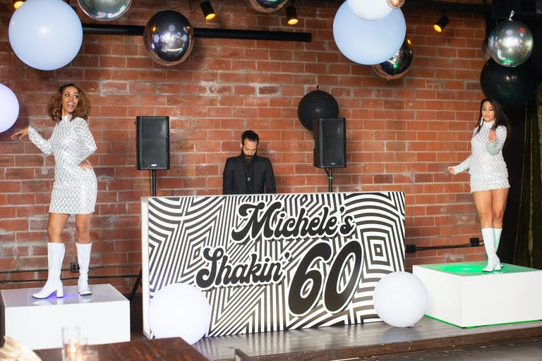 A DJ stand with a 60s theme and two 60s dancers on either side on a raised platform