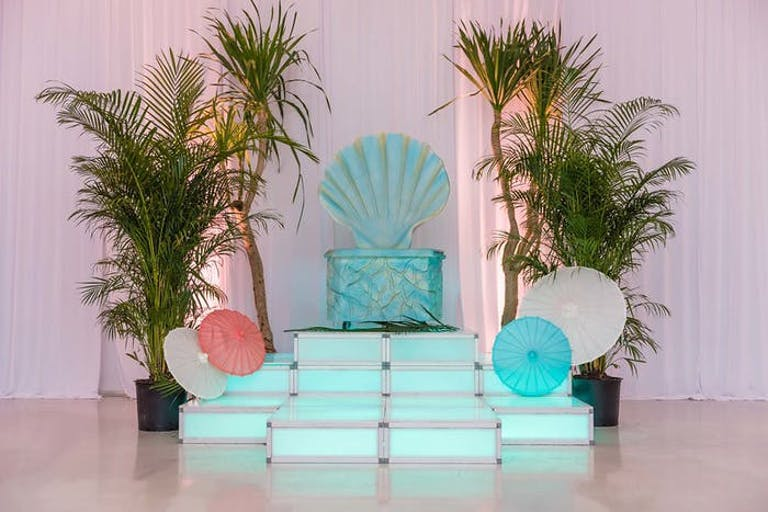 A throne style seat made to look like a giant sea shell with blue footstools in front. Leaves sit on either side of this.