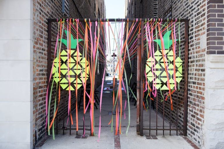 An alley way with streamers hanging from the gates and pineapple pinned