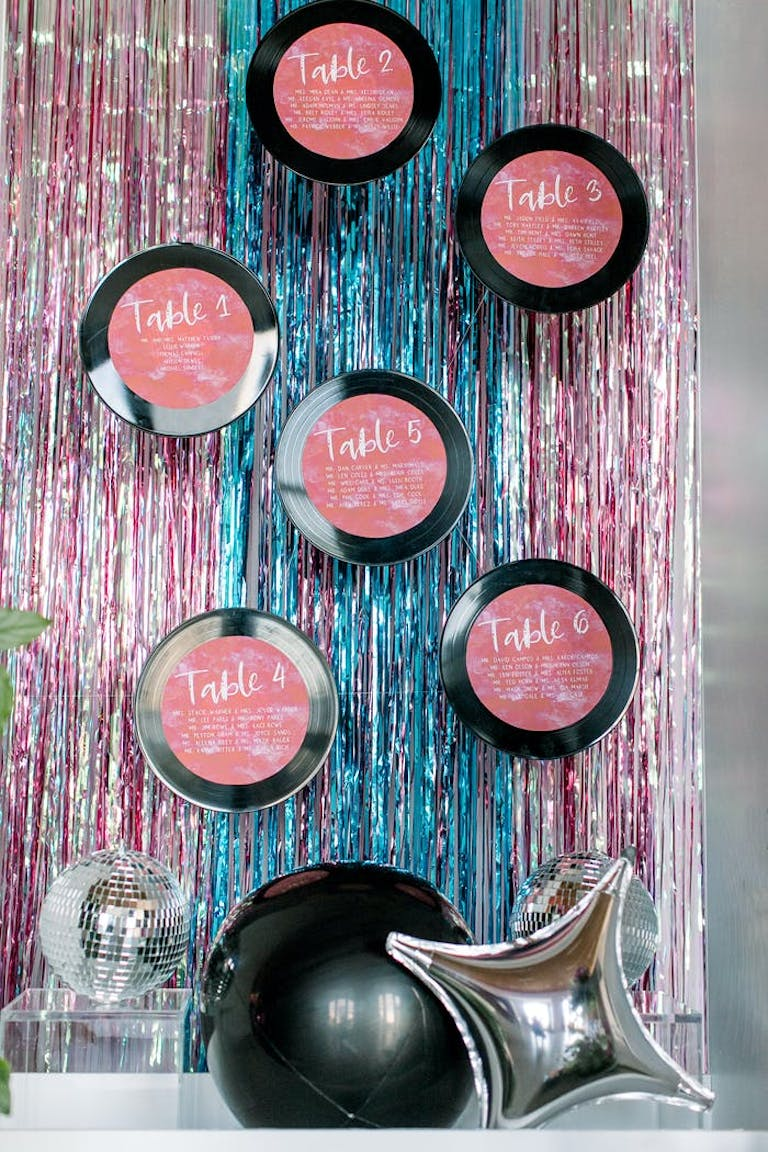 pink and black compacts on top of shiny drape linens for disco theme party | partySlate