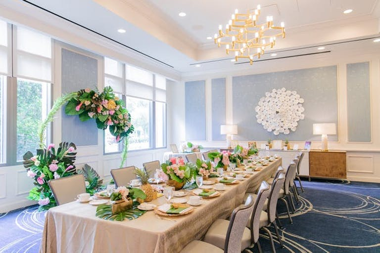 A room with white and powder blue walls. A long table with a beige and white linen and chairs on either side. Clusters of greenery are in the centerpiece and around the room