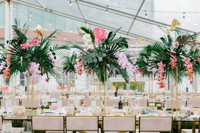 A transparent tend with long tables underneath. Beige chairs along the tables and tall greenery with pink accents as centerpieces.